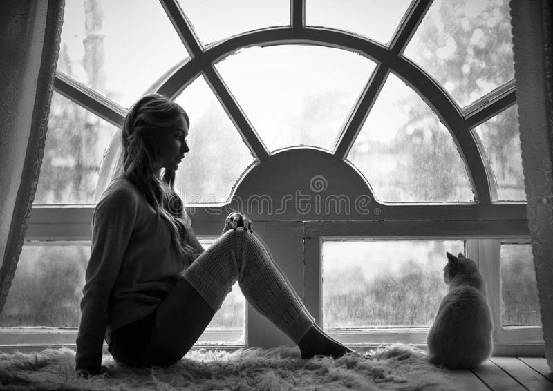 Art photo blond girl and white cat sitting at big old window during the rain. Romantic Black and white photo, loneliness stock photos