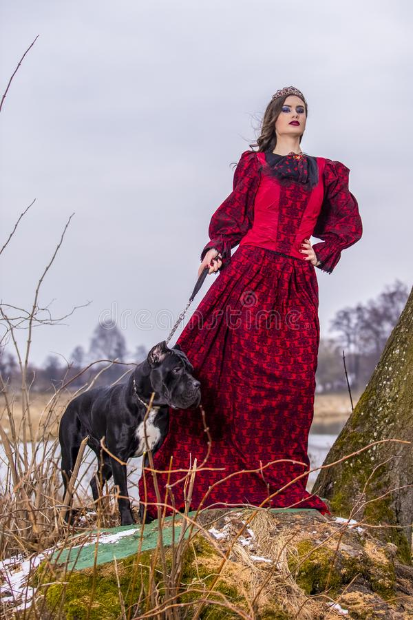 Art Photography Concepts Belle princesse féerique dans la robe rouge avec la couronne et son chien sur la laisse dans la forêt su images libres de droits
