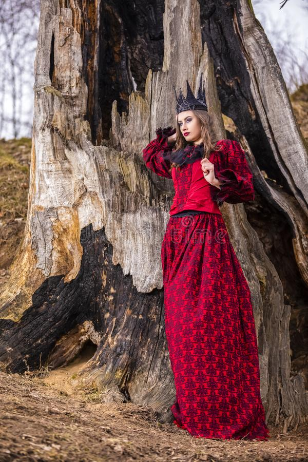 Art Photography Concepts. Mysterious Beautiful Fairy Medieval Princess in Red Dress and Spiky Black Crown in Forest in Early royalty free stock images