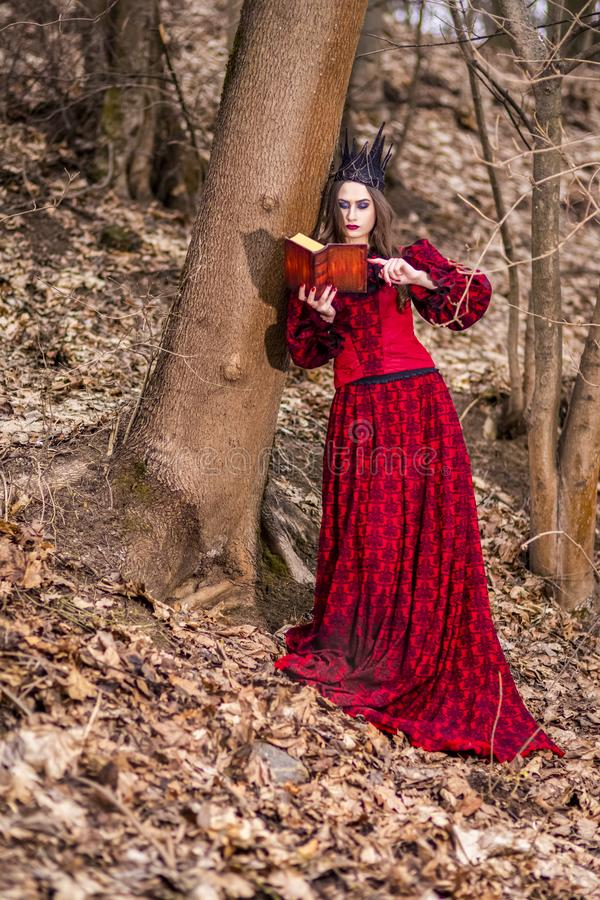 Art Photography. Gorgeous Mysterious Fairy Princess in Red Dress and Black Crown With Old Book. Posing in Forest Outdoors royalty free stock image