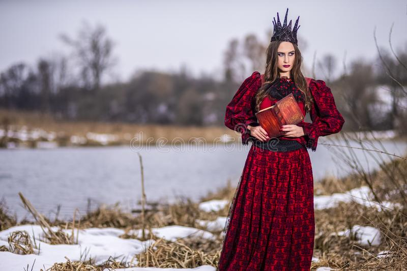 Art Photography Ideas. Mysterious Fairy Princess in Red Dress and Black Crown Reading Old Book. Posing in Forest Outdoors royalty free stock photos