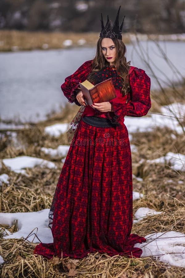 Art Photography Ideas Mystisk felik prinsessa i röd klänning och svart krona som läser den gamla boken Posera i Forest Outdoors royaltyfri foto