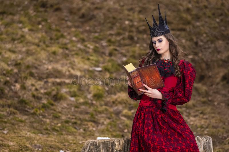 Art Photography. Mysterious Fairy Medieval Queen in Red Dress and Spiky Black Crown Posing With Ancient Book in Forest in Early stock images