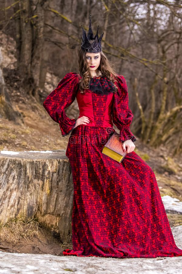 Art Photography. Mysterious Medieval Queen in Red Dress and Spiky Black Crown Posing With Ancient Book in Forest in Early Spring royalty free stock photo