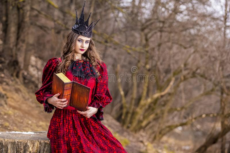 Art Photography. Mysterious Medieval Queen in Red Dress and Spiky Black Crown Posing With Ancient Book in Forest in Early Spring royalty free stock photos