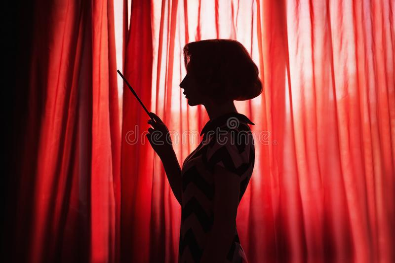 Art photography. Retro silhouette of girl in front of window. Noir photo. Woman smoking a cigarette in mouthpiece. Model with. Cigarette on red background. Noir stock photos