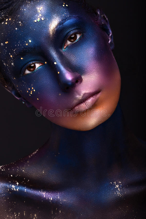 Art portrait of a beautiful girl with color paint on her face stock image