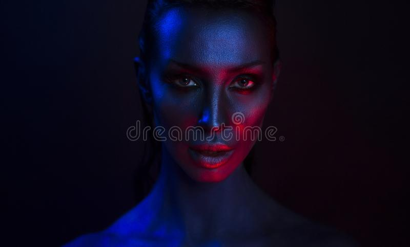 Art Portrait of Beautiful Young Woman with glamorous mystic. Female Art Portrait. Beautiful Young Woman with glamorous mystical makeup in Nightclub. Girl smoking stock photography