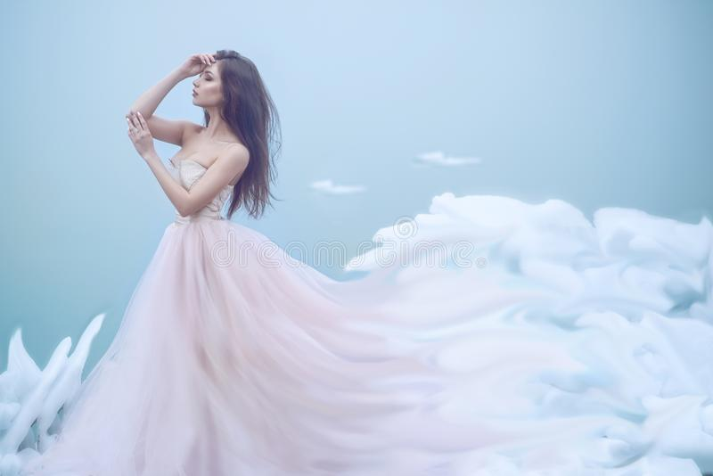 Art portrait of a beautiful young nymph in luxurious strapless ball dress growing into soft clouds royalty free stock image