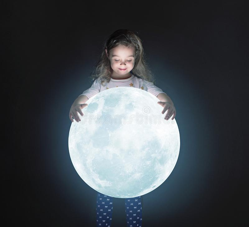 Art portrait of a cute little girl holding a moon stock photo
