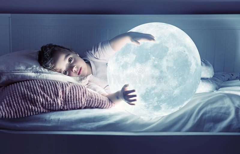 Art portrait of a cute little girl holding a moon stock photos