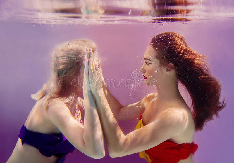 Art portrait of two beautiful pretty girls holding each other hands underwater royalty free stock image
