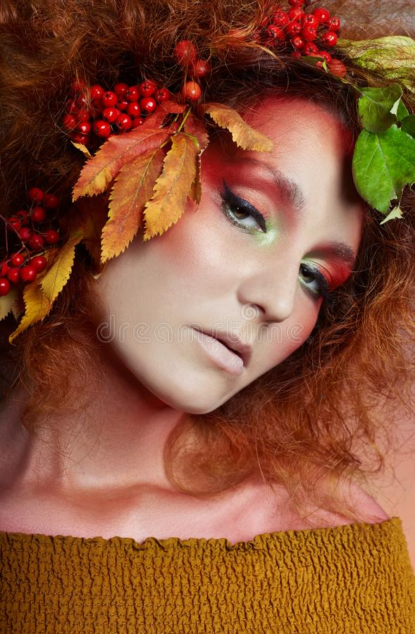 Art portrait of women autumn in her hair, vivid fall colors and makeup, red curly hair and voluminous hair. Leaves and berries. Art portrait of woman autumn in stock photo