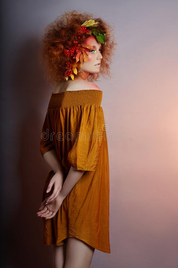 Art portrait of women autumn in her hair, vivid fall colors and makeup, red curly hair and voluminous hair. Leaves and berries. Art portrait of woman autumn in stock photos