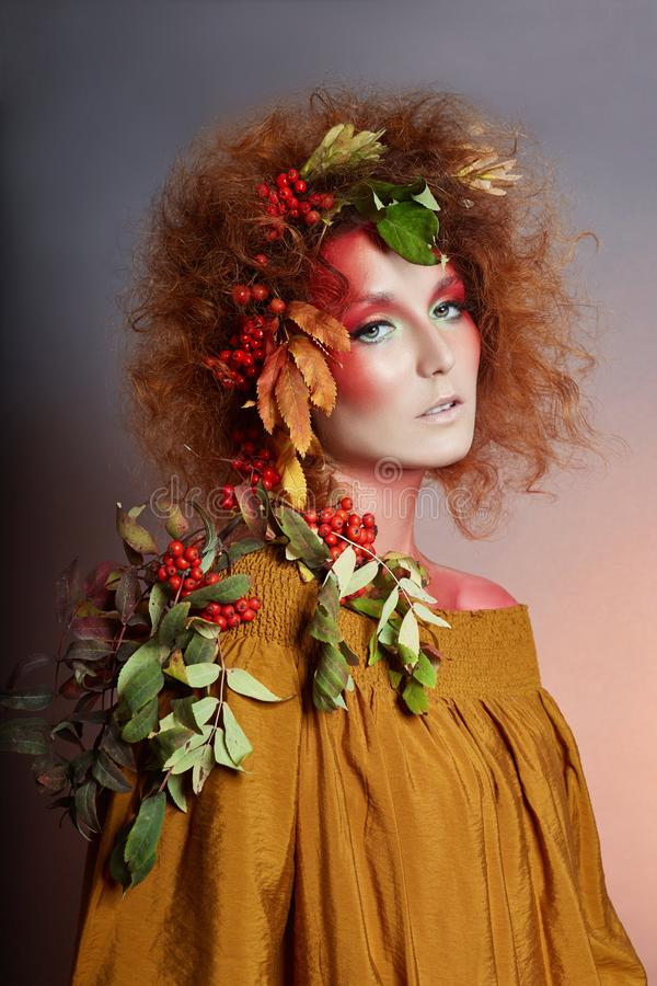 Art portrait of women autumn in her hair, vivid fall colors and makeup, red curly hair and voluminous hair. Leaves and berries. Art portrait of woman autumn in royalty free stock photos