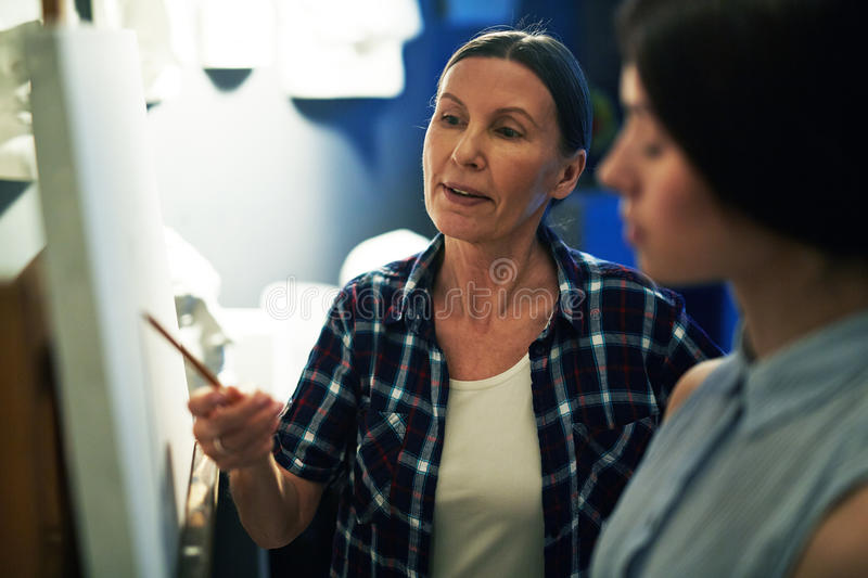 Art Professor Teaching Student to Paint. Portrait of mature women professor helping student to draw, discussing work and explaining mistakes stock photos
