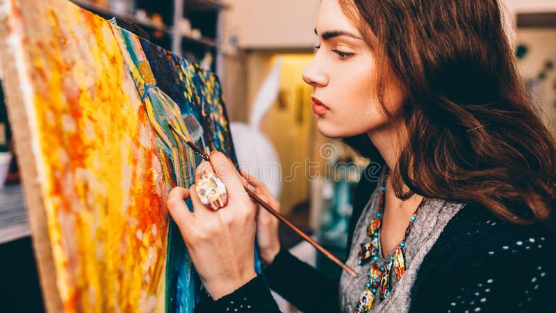 Art school class painter creating abstract artwork. Art school class. Side view of lefthanded female painter creating colorful abstract artwork in studio royalty free stock photography