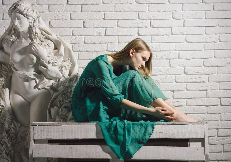 Art school education and master class of fine art. Art and sculpture. Woman artist dream and think at gypsum sculpture. At workshop on white brick wall royalty free stock photography