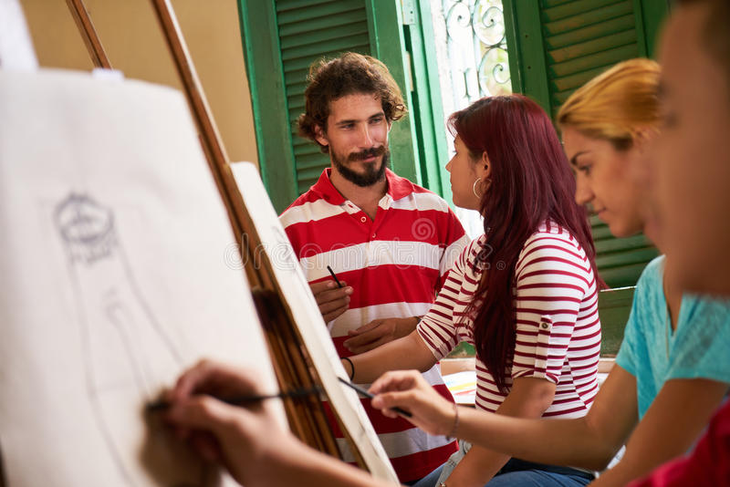 Art School With Teacher And Students Painting In Class. School of art, college of arts, education for group of young students. Professor helping student, men at royalty free stock image