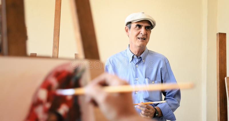Art School With Teacher Talking To Student Painting. Senior people painting for hobby. Group of active seniors at art school. Old men working as teacher royalty free stock photos