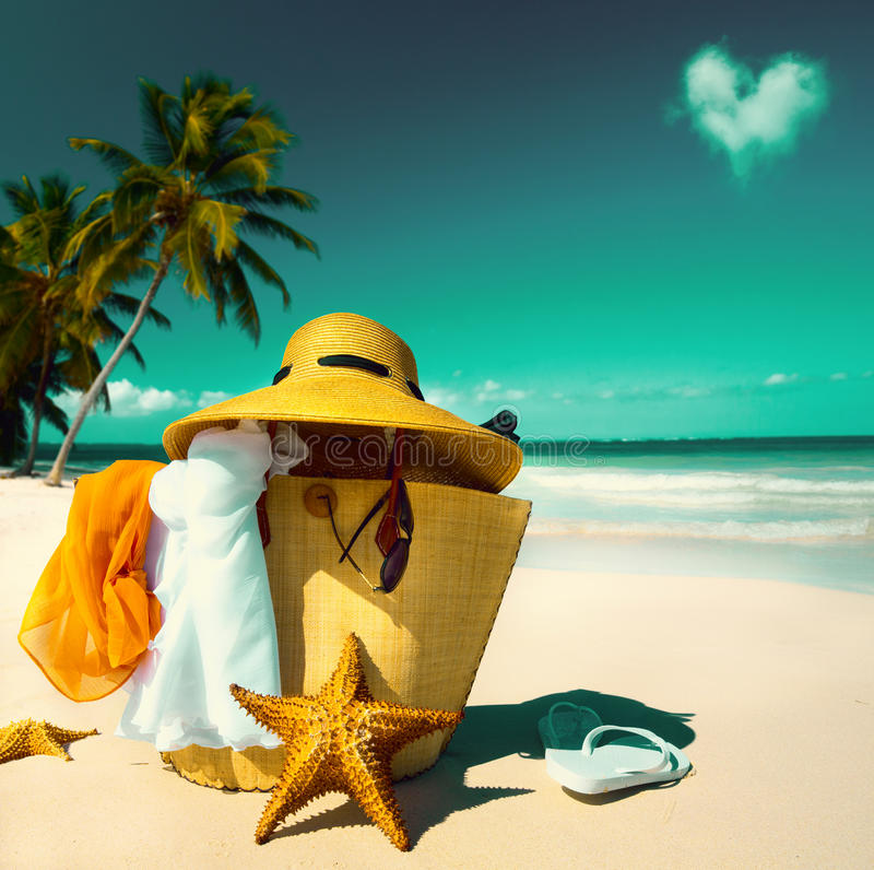 Art Straw hat, bag, sun glasses and flip flops on a tropical beach royalty free stock photos