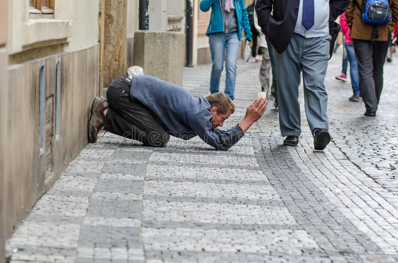Art of street begging in Prague. Prague, Czech Republic - September 26, 2014: Beggar working in the Old Town. It seems he does not expect anything stock photos