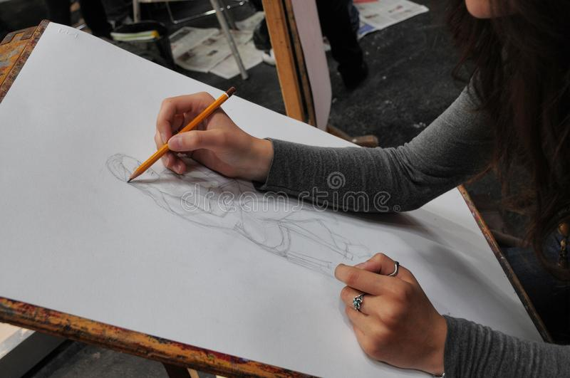 Art student close-up hands at desk drawing with pencil stock image