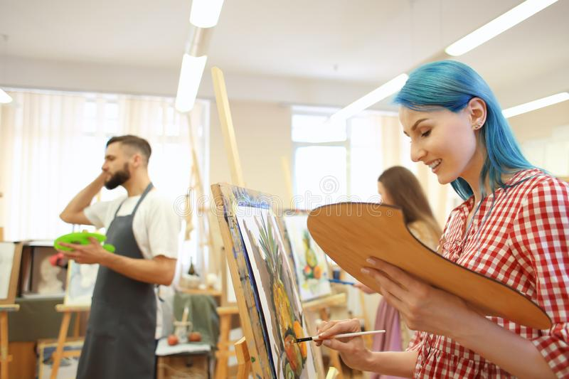 Art students painting in workshop stock images