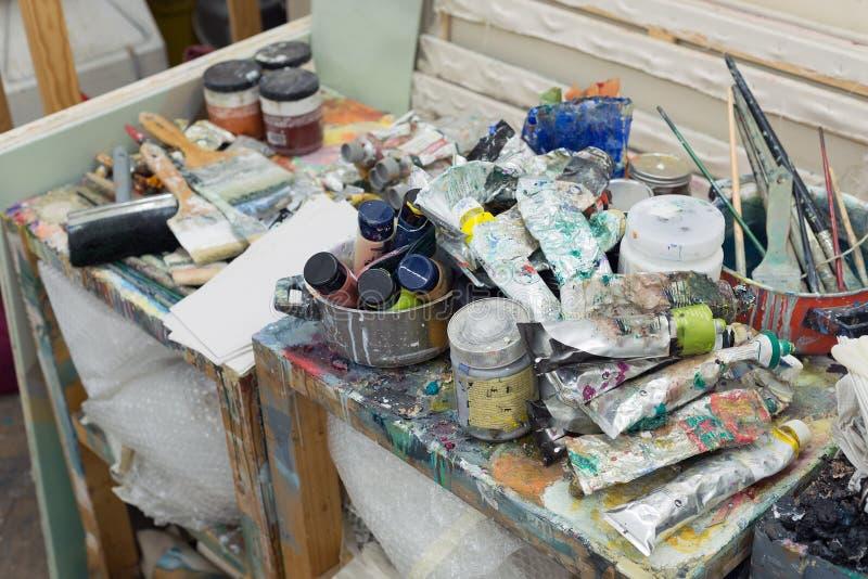 Art studio atelier table full of used artistic oil paint tube brush equipment workshop. Background stock photo
