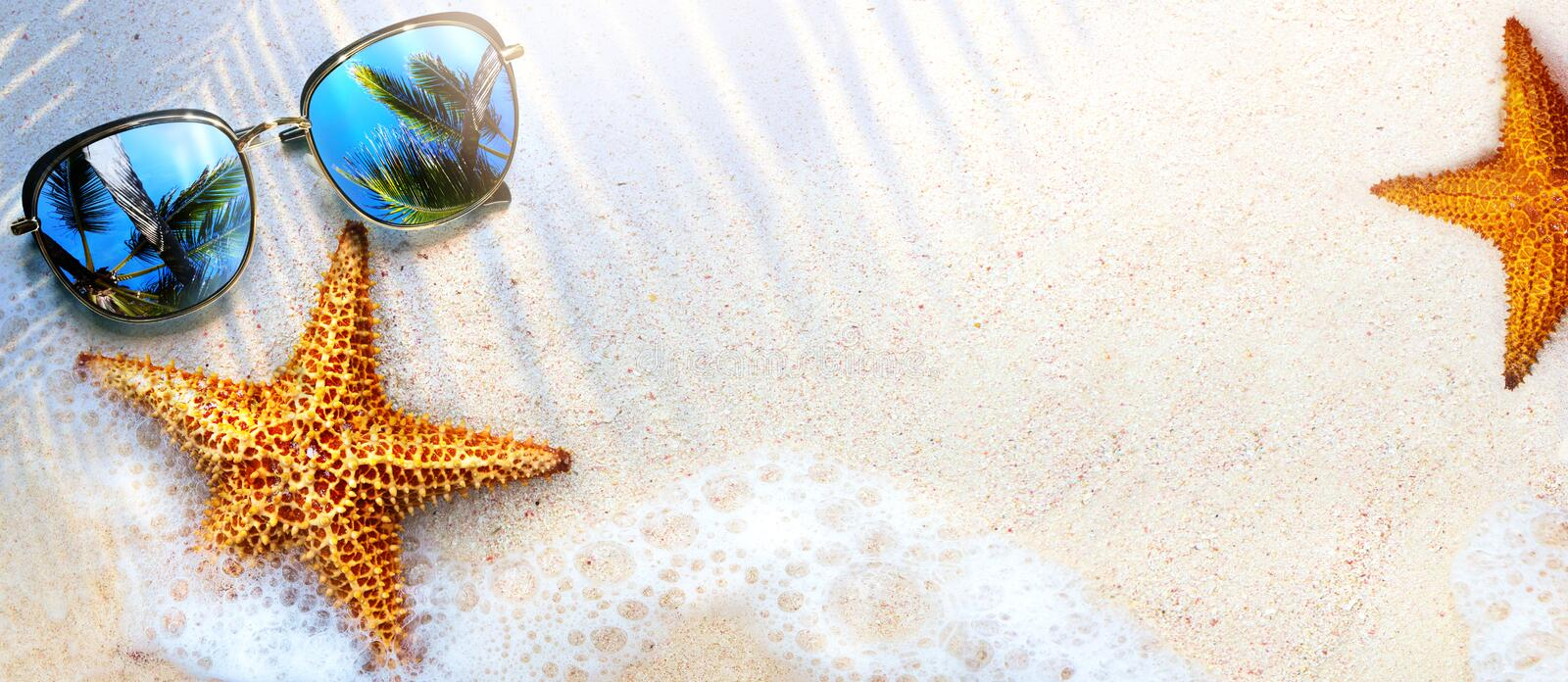 Art Summer Beach background with sunglass and starfish on sand; Tropical sea vacation concept royalty free stock images
