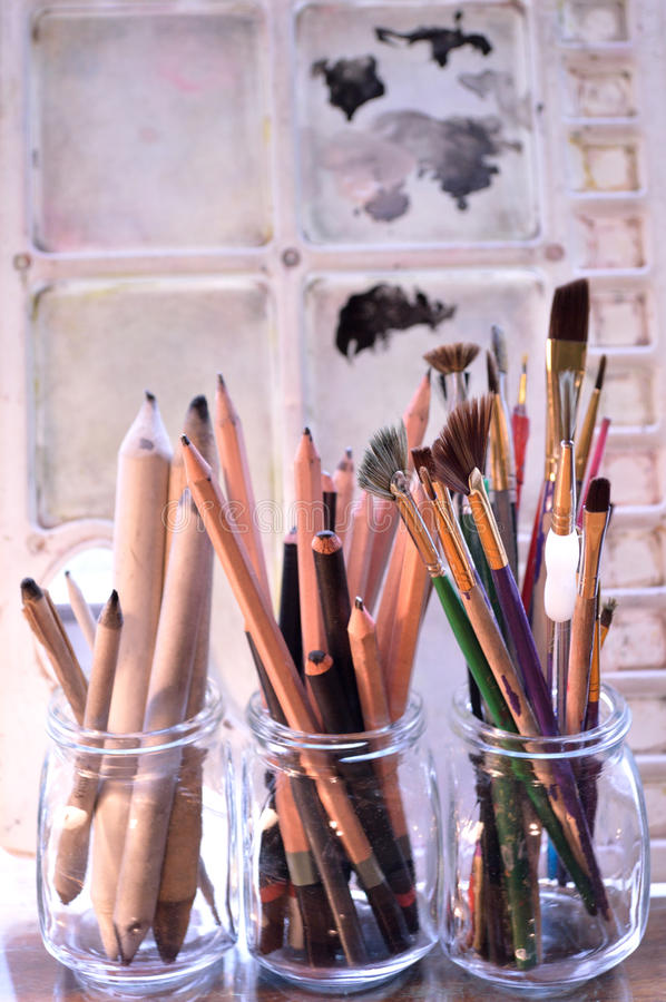 Art supplies in front of art palette. Painting,drawing and sketching tools. Graphite and charcoal pencils for fine art in the middle and blending stumps or stock photography