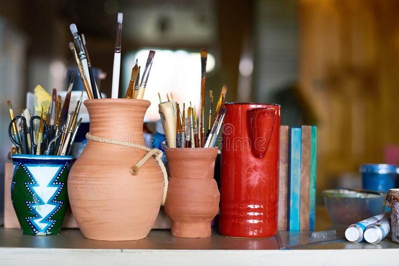 Art Supplies in Pottery Studio. Still life background of several clay pots with paintbrushes and art supplies on table in small art and craft studio royalty free stock photos