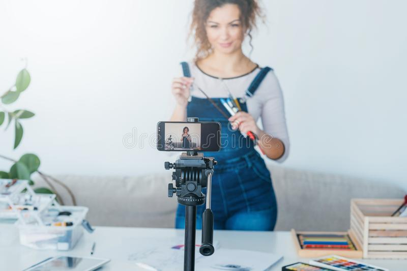 Art supplies promotion blogger record video. Art supplies promotion. Female blogger using smartphone camera to record video about painting tools. Copy space stock image