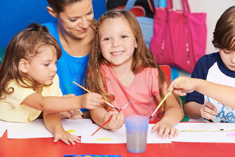 Art teacher and children painting in school. Art teacher and children painting images together in elementary school stock photo