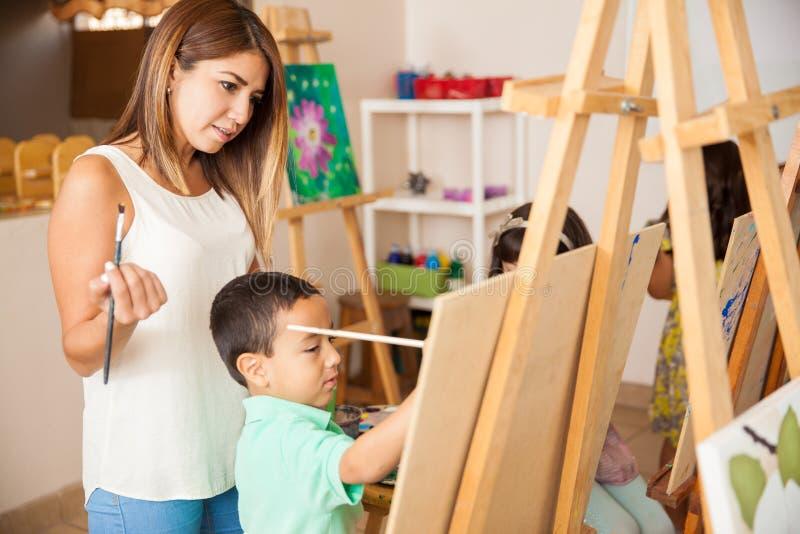 Art teacher grading some work. Pretty Hispanic art teacher reviewing and grading the work of a little boy during class royalty free stock photo