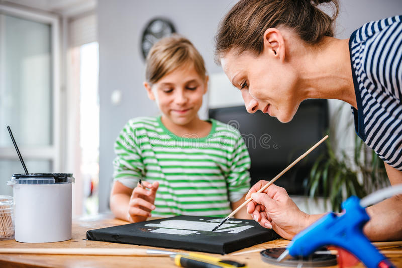 Art teacher helping a student with painting stock image