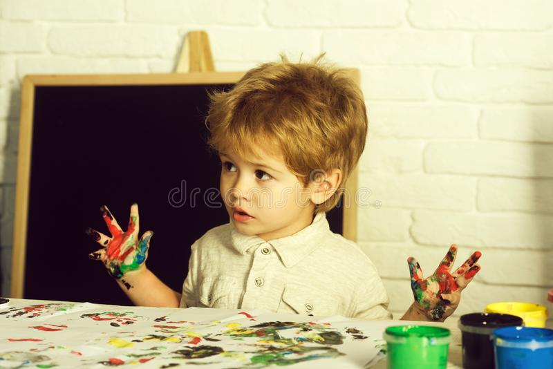 Art therapy. Drawing as a treatment for frustration. The boy draws his fingers. Child with paints. royalty free stock photography