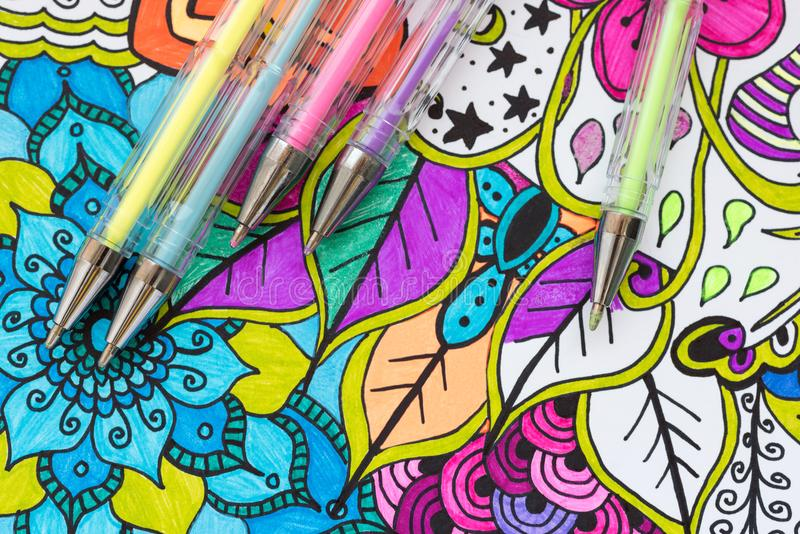 Art therapy, mental health, creativity and mindfulness concept. Adult coloring page with pastel colored gel pens, Flat lay. Adult coloring book, new stress stock photography