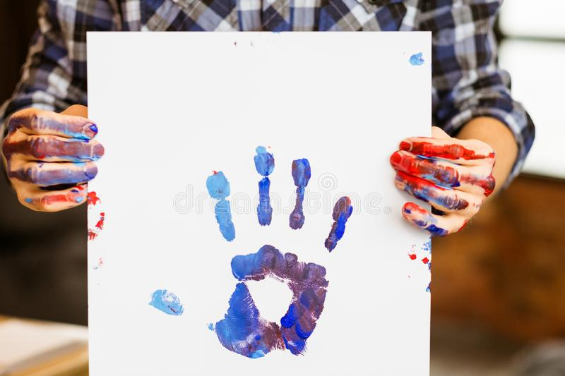 Art therapy school poster hand print education. Art therapy class school. Man holding A3 poster colorful hand print on. Artist hands smeared with paint. Hobby stock images