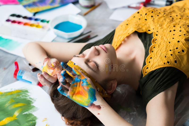 Art therapy tired young lady floor hands paint. Art therapy. Tired young lady lying down on floor with her eyes closed, hands dirty with colorful paint stock photography