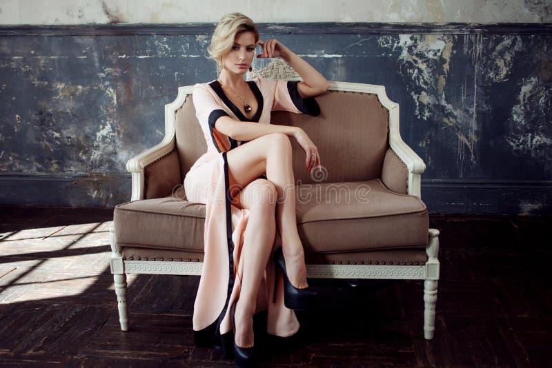 Art und Weisebaumuster mit dem blonden Haar Junge attraktive Frau, stationierend auf dem Sofa, Weinleseart stockfotos