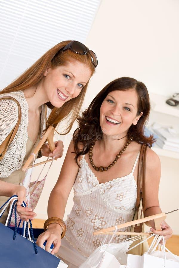 Art und Weiseeinkaufen - Frau zwei wählen Verkaufskleidung lizenzfreies stockbild