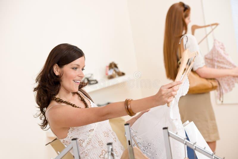 Art und Weiseeinkaufen - Frau zwei wählen Verkaufskleidung lizenzfreies stockfoto