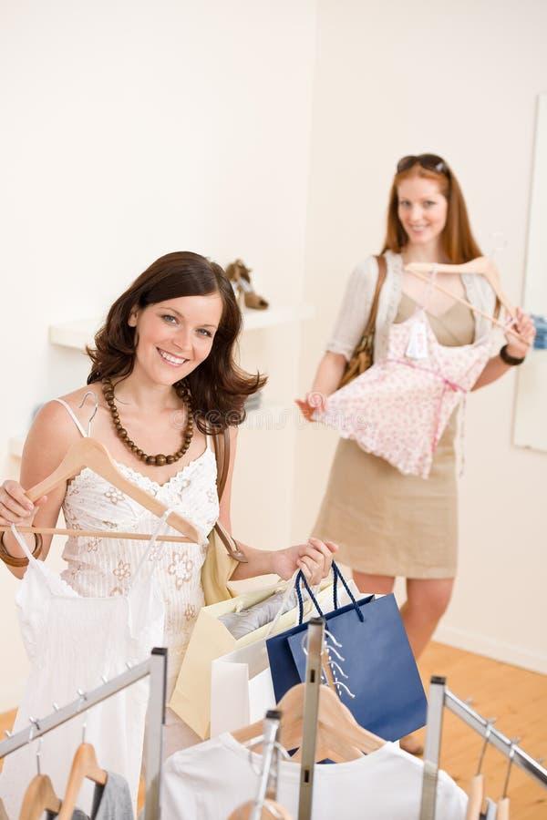 Art und Weiseeinkaufen - Frau zwei wählen Verkaufskleidung lizenzfreie stockfotos