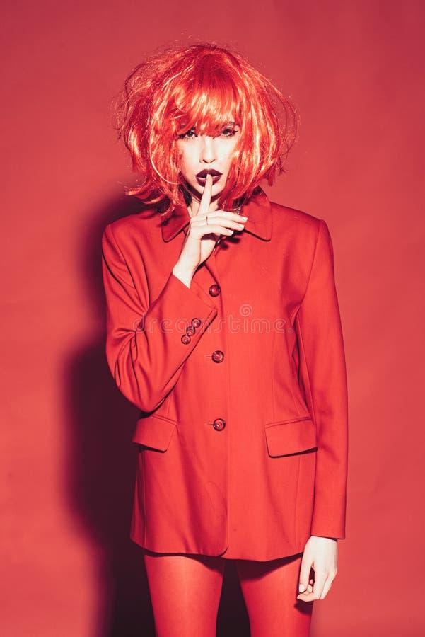 Art und Weisekonzept Dame mit den dunklen Lippen, die Kamera mit Ruhegeste betrachten Mädchen auf mysteriösem Gesicht in rotem fo stockfotos