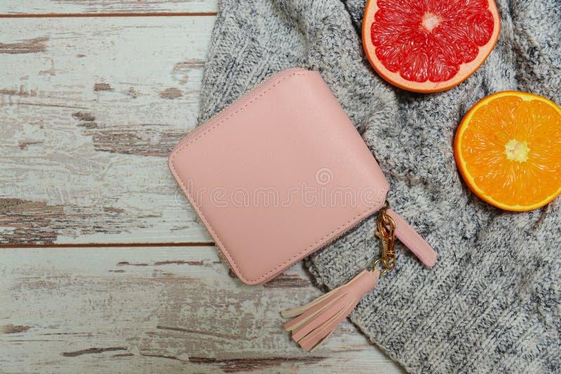 Art und Weisekonzept Kleiner rosa Frauen ` s Geldbeutel, eine Strickjacke und Zitrusfrucht auf einem hölzernen Hintergrund lizenzfreie stockfotos