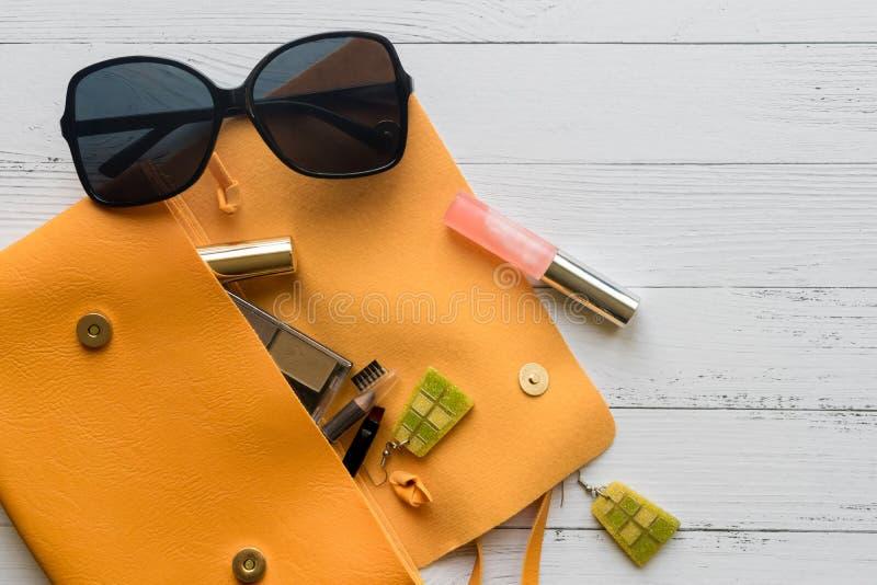 Art und Weisekonzept Weibliche Sachen, kosmetische Produkte, sunglass, Ohrringe und orange Handtasche auf h?lzernem Hintergrund m stockfotos