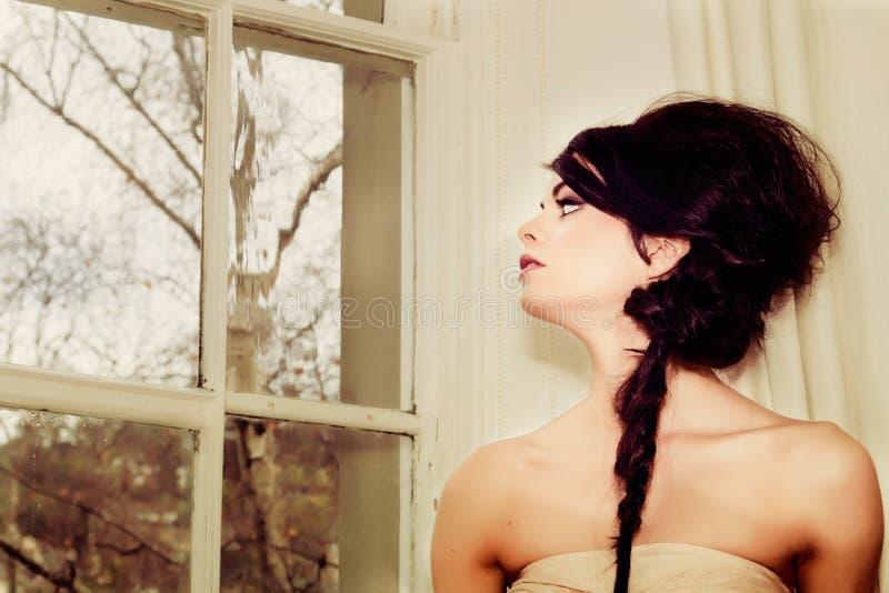 Art und Weisemädchen durch Fenster stockfotografie