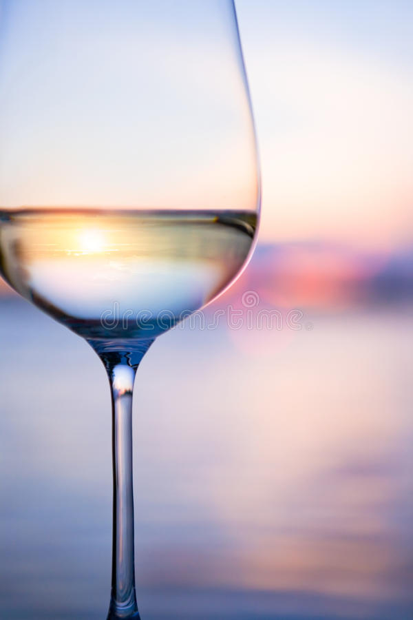 Art white wine on the sky background. A glass of white wine on the background of the sunset