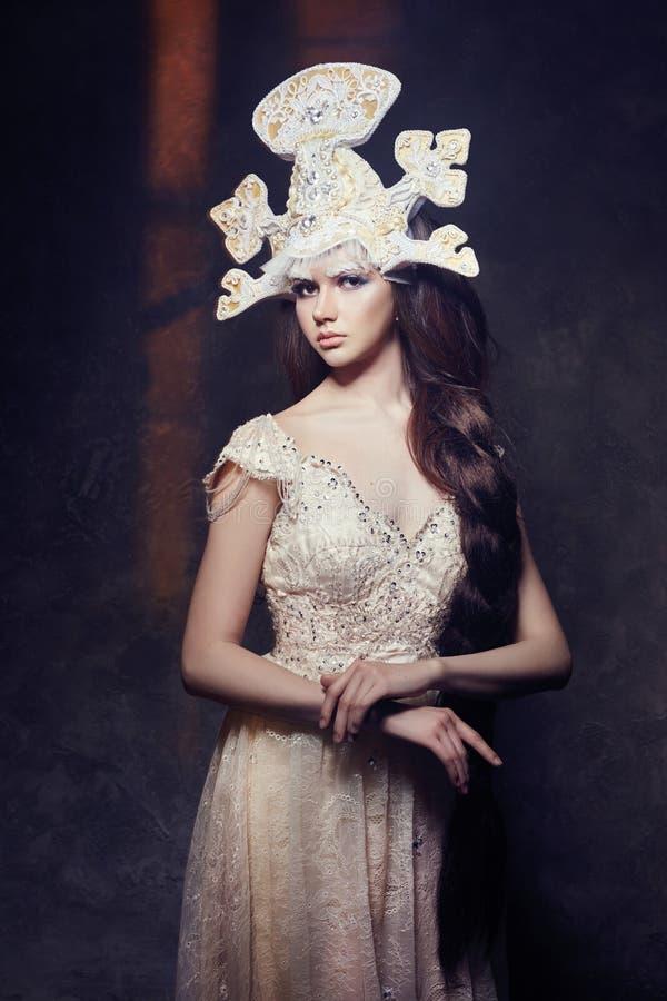 Art Woman avec une longue tresse dans une longue robe luxueuse et un casque fabuleux Reine de neige de fille posant sur un fond f photos stock